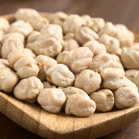 garbanzo bean: Raw chickpeas or garbanzo beans on small wooden plate, photographed with natural light (Selective Focus, Focus one third into the image)