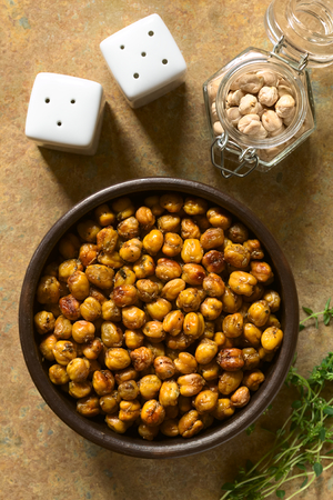 garbanzo bean: Chickpeas roasted with thyme, oregano, salt and pepper, photographed overhead on slate with natural light (Selective Focus, Focus on the chickpeas)