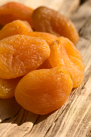 frutos secos: Dried apricots, a healthy snack containing vitamin, beta-carotene, fiber, antioxidants, photographed on wood with natural light (Selective Focus, Focus on the first apricot)