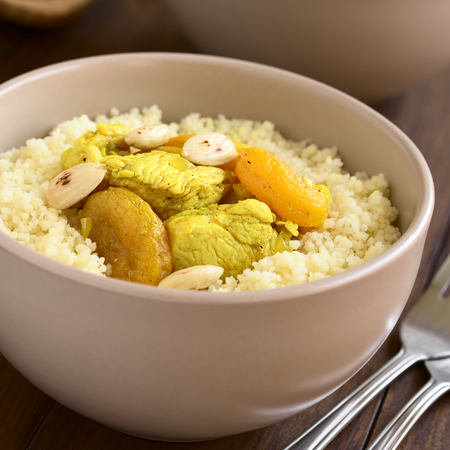 durum wheat semolina: Chicken and dried apricot stew, seasoned with turmeric, cinnamon and honey, served on couscous with roasted almonds, photographed with natural light (Selective Focus, Focus in the middle of the dish)