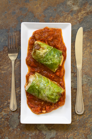 filled roll: Vegetarian baked stuffed savoy cabbage roll filled with wholegrain rice, pepper, onion and carrot, served on tomato sauce on plate, photographed overhead on slate with natural light (Selective Focus, Focus on the dish)