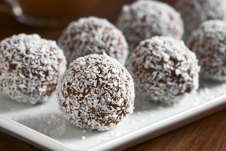 Homemade coconut rum balls on plate, photographed with natural light (Selective Focus, Focus on the first ball)