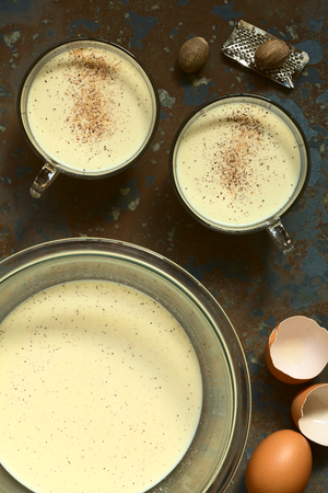 eggnog: Eggnog drink in bowl and two glass cups with ground nutmeg on top, photographed overhead on slate with natural light