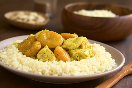 durum wheat semolina: Chicken and dried apricot stew, seasoned with turmeric, cinnamon and honey, served on couscous on plate, photographed with natural light (Selective Focus, Focus in the middle of the dish)