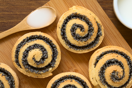 spoonful: Homemade poppy seed rolls on wooden board with a spoonful of frosting, photographed overhead with natural light