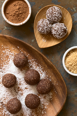Coconut rum balls being covered with grated coconut on wooden plate, ingredients (cocoa powder, cookies) on the side, photographed overhead on slate with natural light