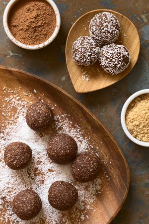 Kokos rum ballen worden bedekt met geraspte kokos op houten plaat, ingrediënten (cacaopoeder, koekjes), aan de kant, gefotografeerd overhead op leisteen met natuurlijk licht Stockfoto