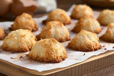 Zelfgemaakte coconut bitterkoekjes (kokosnoot meringue cookies), traditionele koekjes van Kerstmis in Duitsland genaamd Kokosmakronen, gefotografeerd met natuurlijk licht (Selective Focus, Focus op de voorkant van de eerste bitterkoekjes) Stockfoto