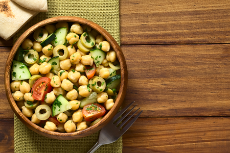 garbanzo bean: Chickpea salad with green olives, cucumber, cherry tomato and parsley, served in wooden bowl, pita bread pieces on the side, photographed overhead with natural light
