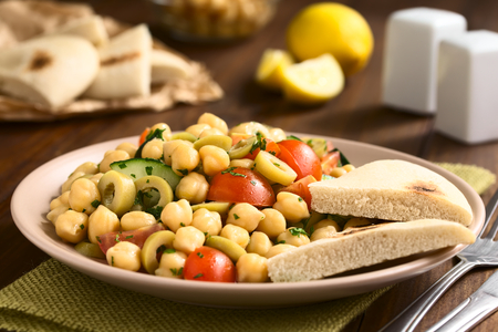 chickpea: Chickpea salad with green olives, cucumber, cherry tomato and parsley, served on plate with pita bread pieces on the side, photographed with natural light (Selective Focus, Focus one third into the salad) Stock Photo