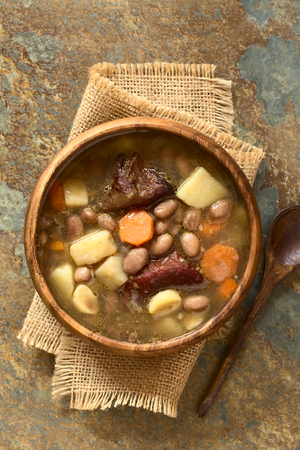 pinto bean: Traditional Hungarian Babgulyas bean goulash, a soup made of pinto beans, smoked meat, potato, carrot, csipetke homemade soup pasta, garlic, onion, served in wooden bowl, photographed overhead on slate with natural light