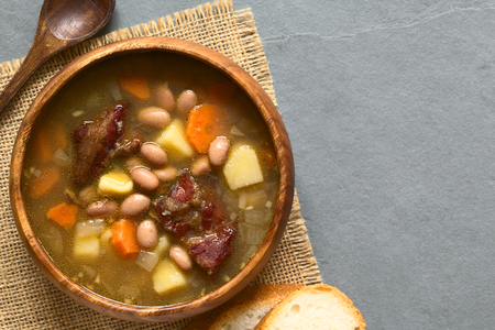 pinto: Traditional Hungarian Babgulyas bean goulash, a soup made of pinto beans, smoked meat, potato, carrot, csipetke homemade soup pasta, served in wooden bowl, photographed overhead on slate with natural light