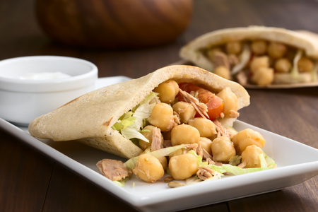 garbanzo bean: Pita sandwich stuffed with chickpea, tuna, lettuce, pepper, cherry tomato, roasted sunflower seeds on top, photographed with natural light (Selective Focus, Focus one third into the image) Stock Photo
