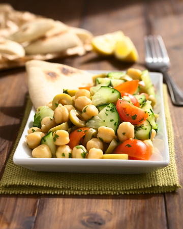 garbanzo bean: Chickpea salad with green olives, cucumber, cherry tomato and parsley, served on plate with pita bread pieces in the back, photographed with natural light (Selective Focus, Focus one third into the salad)