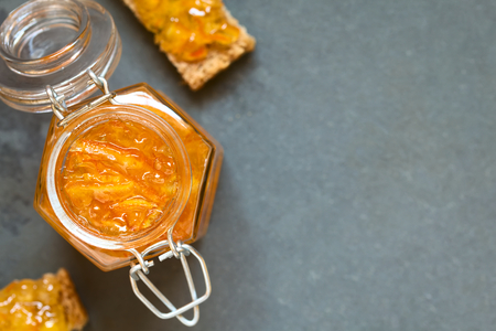 Orange jam in swing-top jar, bread slices with orange jam on the side, photographed overhead on slate with natural light (Selective Focus, Focus on the orange jam in the jar)