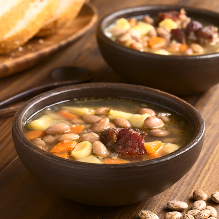 pinto: Traditional Hungarian Babgulyas bean goulash, a soup made of pinto beans, smoked meat, potato, carrot, csipetke homemade soup pasta, served in rustic bowls, photographed with natural light Selective Focus, Focus on the meat
