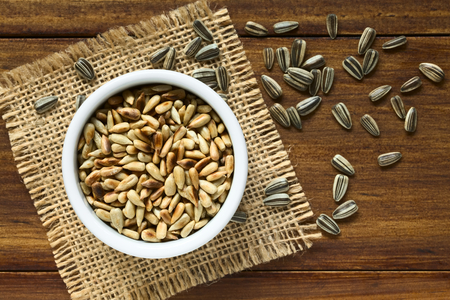 hull: Roasted sunflower seeds in small bowl surrounded by whole seeds with hull, photographed overhead on wood with natural light (Selective Focus, Focus on the top of the roasted seeds) Stock Photo