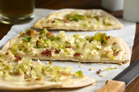 cut paper: Homemade leek and bacon tarte flambee, a traditional French and German oven baked pizza-like pie, photographed on parchment paper with natural light Selective Focus, Focus on the front of the middle slice Stock Photo