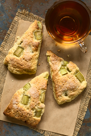 scone: Homemade rhubarb scones with a cup of tea photographed overhead with natural light