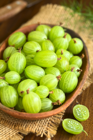 ribes: Raw gooseberries (lat. Ribes uva-crispa) in bowl photographed on dark wood with natural light Stock Photo
