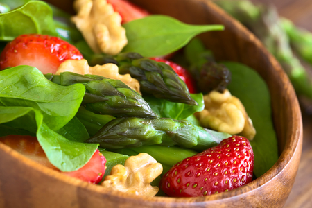 baby spinach: Fresh strawberry, green asparagus, baby spinach and walnut salad served in wooden bowl, photographed with natural light