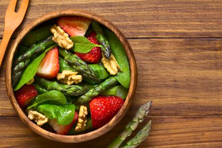 新鮮なイチゴ、グリーン アスパラガス、ほうれん草、クルミ木製ボウルに、野菜サラダ撮影自然光とダークウッドのオーバーヘッド