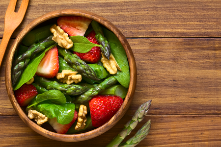 Fresh strawberry, green asparagus, baby spinach and walnut salad served in wooden bowl, photographed overhead on dark wood with natural light