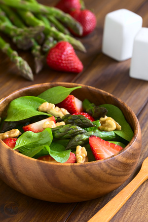 spinach salad: Fresh strawberry, green asparagus, baby spinach and walnut salad served in wooden bowl, photographed on dark wood with natural light