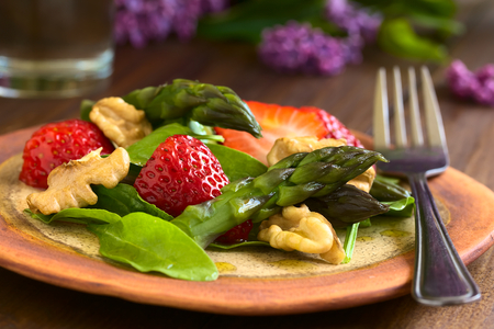 baby spinach: Fresh strawberry, green asparagus, baby spinach and walnut salad served on plate with fork, photographed on dark wood with natural light Stock Photo