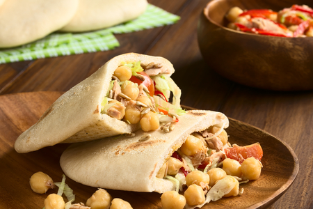 pita bread: Pita sandwich stuffed with chickpea, tuna, lettuce, pepper, cherry tomato, roasted sunflower seeds on top, photographed with natural light (Selective Focus, Focus one third into the stuffing of the upper pita) Stock Photo