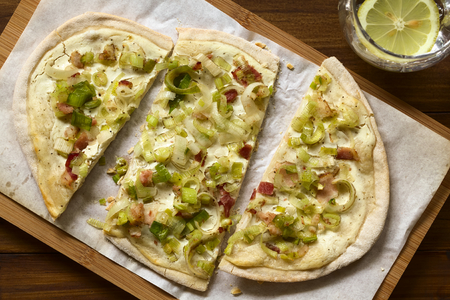 meat pie: Homemade leek and bacon tarte flambee, a traditional French and German oven baked pizza-like pie, photographed overhead with natural light Stock Photo
