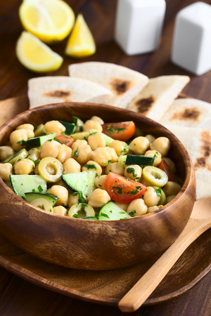 garbanzo bean: Chickpea salad with green olives, cucumber, cherry tomato and parsley, served in wooden bowl, photographed with natural light (Selective Focus, Focus one third into the salad) Stock Photo