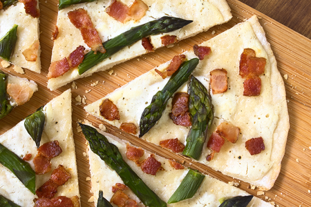 alsatian: Green asparagus and bacon tarte flambee or Flammkuchen, a typical Alsatian and South German dish, photographed overhead on wooden board with natural light Stock Photo