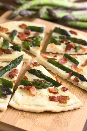 alsatian: Green asparagus and bacon tarte flambee or Flammkuchen, a typical Alsatian and South German dish, photographed on wooden board with natural light (Selective Focus, Focus one third into the image) Stock Photo