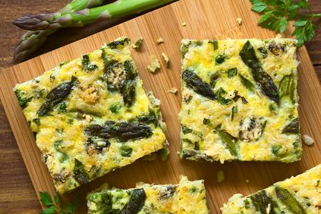 Frittata gemaakt van eieren, groene asperges, erwten, blauwe kaas, peterselie en bruine rijst, gefotografeerd overhead op een houten bord met natuurlijk licht Stockfoto