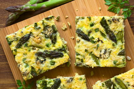 Frittata made of eggs, green asparagus, pea, blue cheese, parsley and brown rice, photographed overhead on wooden board with natural light Stock Photo