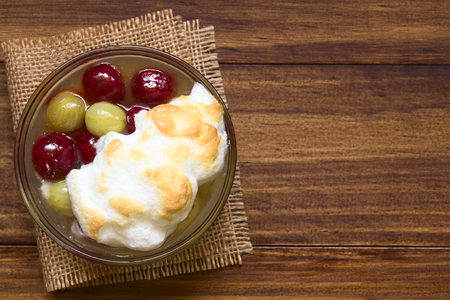 huevo blanco: Stewed red and green gooseberry dessert with meringue in glass bowl, photographed overhead on dark wood with natural light
