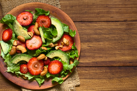 Strawberry, avocado, lettuce salad with cashew nuts on plate, photographed overhead on dark wood with natural light