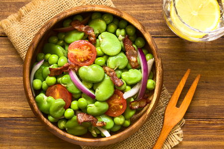 Broad bean, green pea, cherry tomato, red onion and fried bacon salad in wooden bowl, photographed overhead on dark wood with natural light