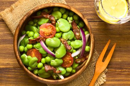 Tuinboon, groene erwten, cherry tomaten, rode ui en gebakken spek salade in houten kom, overhead gefotografeerd op donker hout met natuurlijk licht