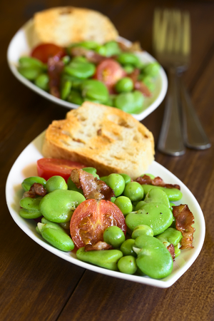 fava: Broad bean, green pea, cherry tomato and fried bacon salad with toasted bread, photographed on dark wood with natural light (Selective Focus, Focus one third into the first salad)