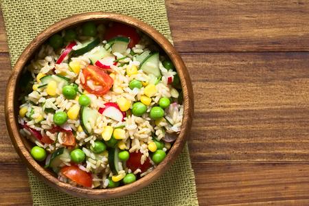 Bruine rijst salade met cherry tomaten, maïs, komkommer, radijs, erwten en bieslook geserveerd in een kom, gefotografeerd overhead op donker hout met natuurlijk licht (Selective Focus, Focus op de top van de salade)