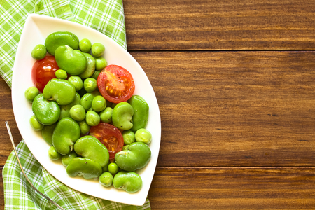 broad bean: Broad bean, green pea and cherry tomato salad, photographed overhead on dark wood with natural light