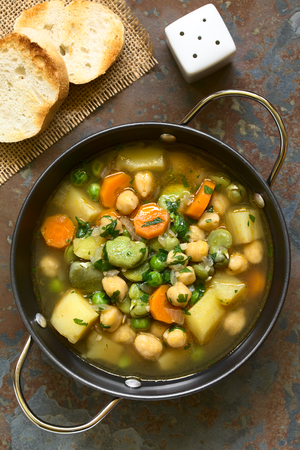 Vegetarian chickpea soup with carrot, broad bean (fava bean), pea, potato, onion, garlic and parsley served in bowl, photographed overhead on slate with natural light Stock Photo