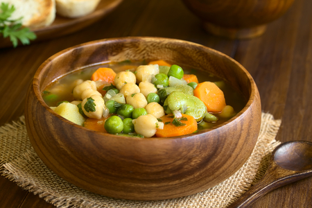 fava bean: Vegetarian chickpea soup with carrot, broad bean (fava bean), pea, potato, onion, garlic and parsley served in wooden bowl, photographed on wood with natural light (Selective Focus, Focus one third into the soup) Stock Photo