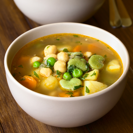 broad bean: Vegetarian chickpea soup with carrot, broad bean (fava bean), pea, potato, onion, garlic and parsley served in bowl, photographed on wood with natural light (Selective Focus, Focus in the middle of the first soup) Stock Photo
