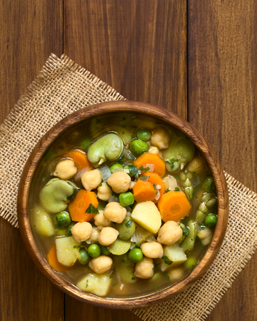 broad bean: Vegetarian chickpea soup with carrot, broad bean (fava bean), pea, potato, onion, garlic and parsley served in wooden bowl, photographed overhead on wood with natural light