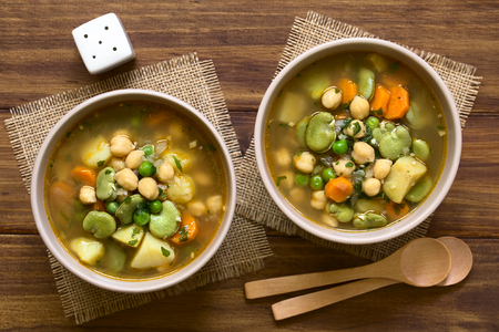 fava bean: Vegetarian chickpea soup with carrot, broad bean (fava bean), pea, potato, onion, garlic and parsley served in bowls, photographed overhead on wood with natural light Stock Photo