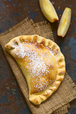 chilean: Chilean apple empanada with icing sugar, photographed overhead on slate with natural light