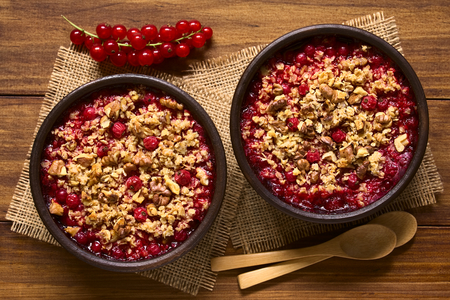 redcurrant: Redcurrant crumble or crisp with oatmeal and walnut on top baked in rustic bowls, photographed overhead on dark wood with natural light (Selective Focus, Focus on the top of the crumbles) Stock Photo